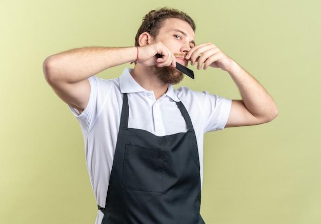 Pewny siebie młody męski fryzjer noszący jednolitą brodę czesaną odizolowaną na oliwkowozielonej ścianie