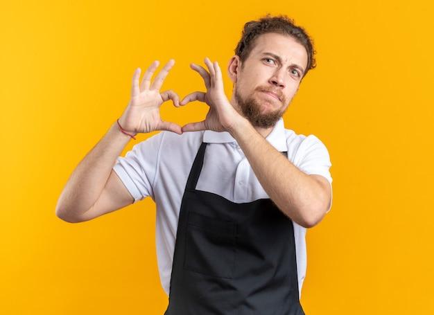 Pewny siebie młody męski fryzjer ubrany w mundur pokazujący gest serca na żółtej ścianie