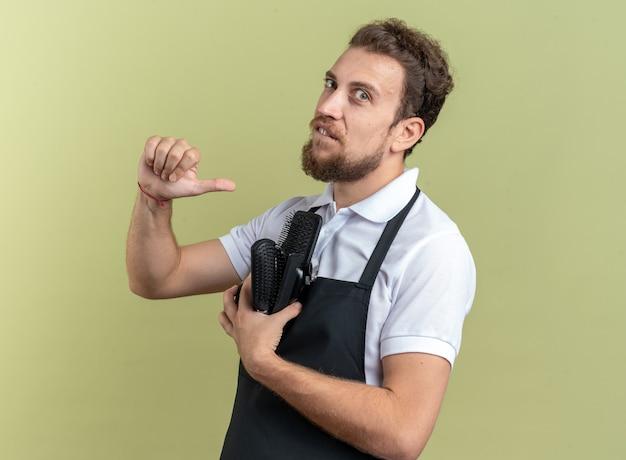 Pewny siebie młody męski fryzjer ubrany w mundur trzymający narzędzia fryzjerskie wskazuje na siebie odizolowanego na oliwkowozielonej ścianie