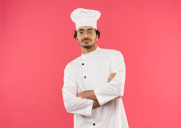 Pewny siebie młody mężczyzna kucharz ubrany w mundur szefa kuchni i okulary skrzyżowane ręce