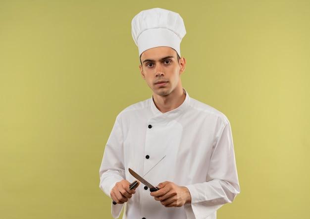Pewny siebie młody mężczyzna kucharz ubrany w mundur szefa kuchni ostrzy nożem na odosobnionej zielonej ścianie