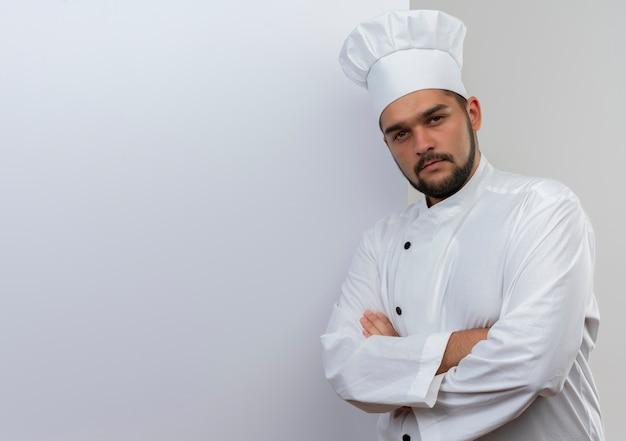 Pewny siebie młody mężczyzna kucharz w mundurze szefa kuchni stojący przed białą ścianą z zamkniętą postawą patrząc odizolowaną na białą ścianę z kopią miejsca