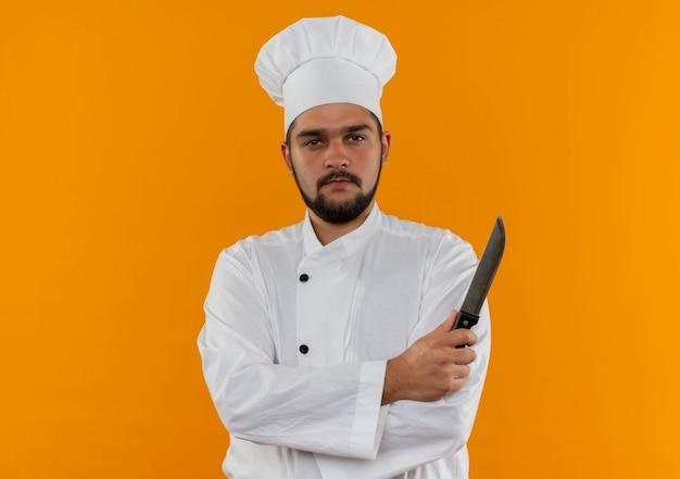 Pewny siebie młody mężczyzna kucharz w mundurze szefa kuchni stojący z zamkniętą postawą i trzymający nóż odizolowany na pomarańczowej ścianie