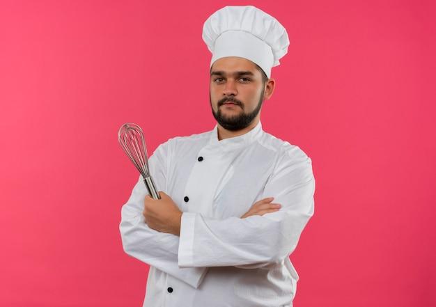 Pewny siebie młody mężczyzna kucharz w mundurze szefa kuchni, stojący z zamkniętą postawą i trzymający trzepaczkę odizolowaną na różowej ścianie