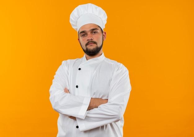 Pewny siebie młody mężczyzna kucharz w mundurze szefa kuchni stojący z zamkniętą postawą odizolowaną na pomarańczowej ścianie z miejscem na kopię