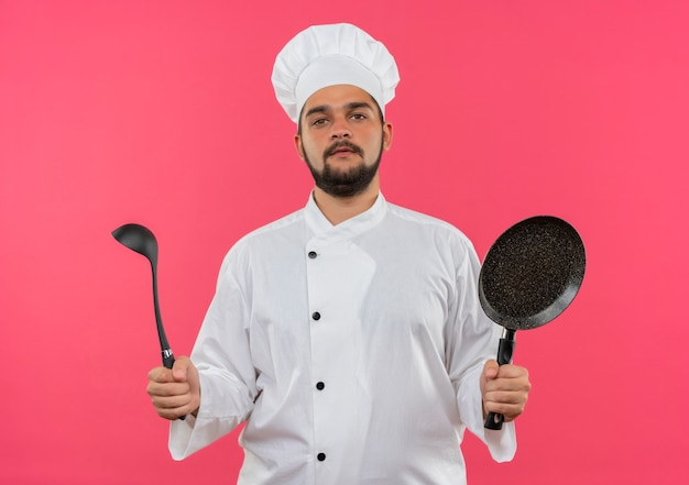 Pewny siebie młody mężczyzna kucharz w mundurze szefa kuchni trzymający kadzi i patelnię na białym tle na różowej ścianie