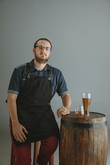 Pewny siebie młody mężczyzna piwowarz z własnym piwem w szkle na drewnianej beczce na szaro