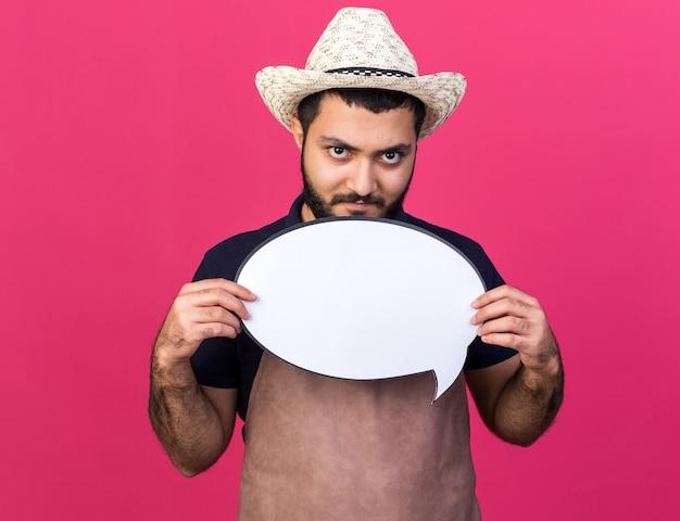Pewny siebie młody mężczyzna rasy kaukaskiej ogrodnik w kapeluszu ogrodniczym trzymający balon mowy odizolowany na różowej ścianie z miejscem na kopię