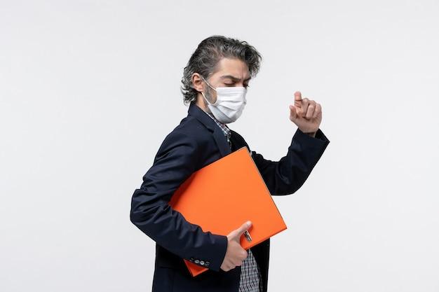 Pewny siebie młody mężczyzna w garniturze i trzymający dokumenty w masce medycznej, zamykający oczy na białej powierzchni