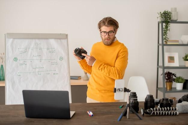 Pewny siebie młody nauczyciel w codziennym ubraniu stoi przy tablicy przed aparatem smartfona i wyjaśnia temat publiczności online
