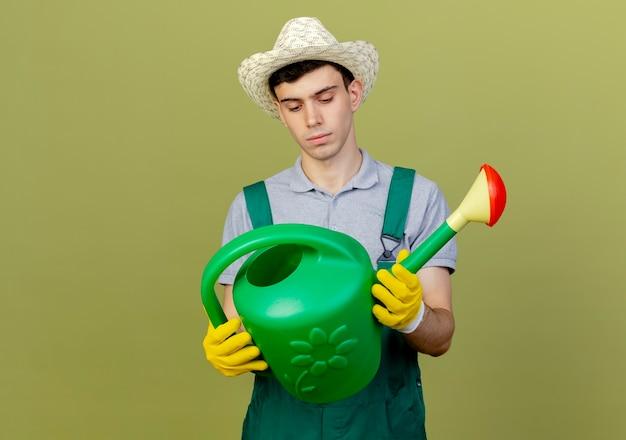 Pewny siebie młody ogrodnik mężczyzna w kapeluszu ogrodniczym i rękawiczkach trzyma i patrzy na konewkę