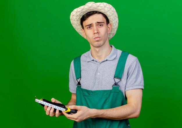 Pewny siebie młody ogrodnik mężczyzna w kapeluszu ogrodniczym mierzy bakłażana z centymetrem