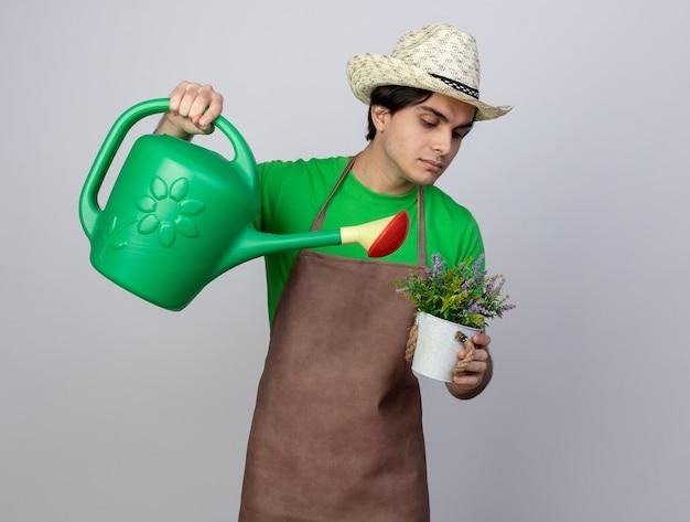 Pewny siebie młody ogrodnik mężczyzna w mundurze na sobie kapelusz ogrodniczy podlewanie kwiatów w doniczce z konewką