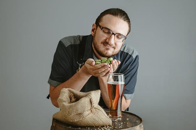 Pewny siebie młody piwowar z własnym piwem w szklance na drewnianej beczce na szarej ścianie