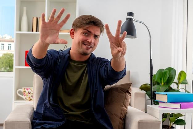 Pewny siebie młody przystojny blondyn siedzi na fotelu, wskazując ósemkę palcami w salonie