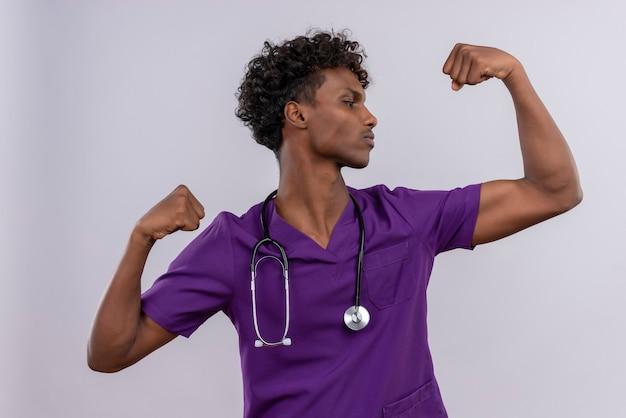 Pewny siebie młody przystojny ciemnoskóry lekarz z kręconymi włosami w fioletowym mundurze ze stetoskopem pokazującym gest siły
