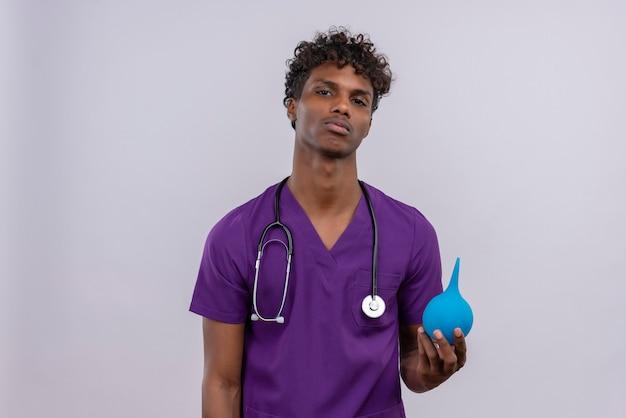 Pewny siebie młody przystojny ciemnoskóry lekarz z kręconymi włosami w fioletowym mundurze ze stetoskopem, trzymając lewatywę