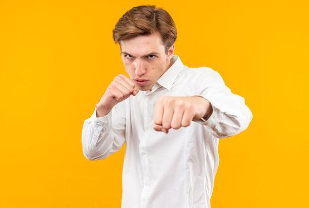 Pewny siebie młody przystojny facet ubrany w białą koszulę stojący w pozie do walki na pomarańczowej ścianie