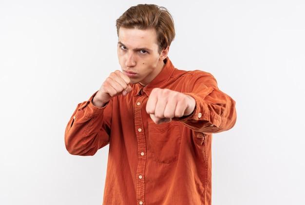 Pewny siebie młody przystojny facet ubrany w czerwoną koszulę stojący w pozie do walki na białym tle na białej ścianie