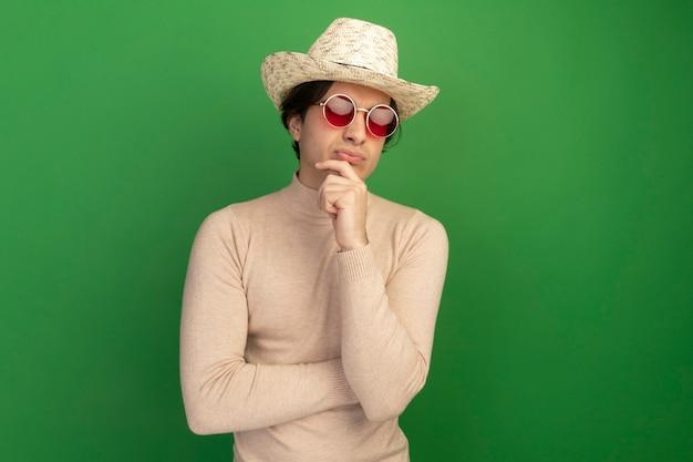 Pewny siebie młody przystojny facet w kapeluszu w okularach chwycił podbródek na zielonej ścianie z kopią przestrzeni