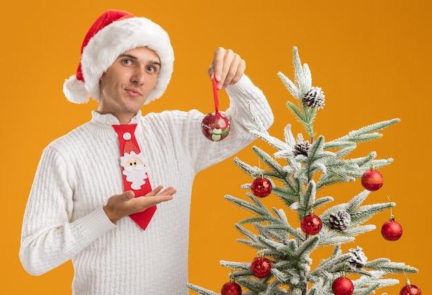 Pewny siebie młody przystojny facet w świątecznym kapeluszu i krawacie świętego mikołaja stojący w pobliżu ozdobionej choinki trzymającej i wskazującej ręką na bombkę świąteczną ozdobę patrzącą na pomarańczową ścianę