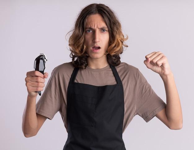 Pewny siebie młody przystojny fryzjer ubrany w mundur trzymający maszynkę do strzyżenia włosów, robiący silny gest