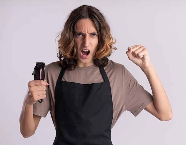 Pewny siebie młody przystojny fryzjer ubrany w mundur trzymający maszynki do strzyżenia włosów, patrzący na przód krzyczy, robiąc być silnym gestem na białej ścianie