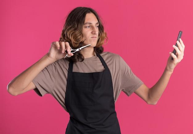 Pewny siebie młody przystojny fryzjer ubrany w mundur trzymający nożyczki przy selfie