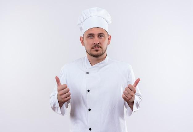 Pewny siebie młody przystojny kucharz w mundurze szefa kuchni pokazując kciuk do góry na białym tle na białej ścianie