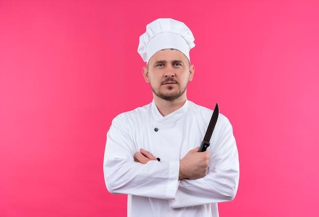 Pewny siebie młody przystojny kucharz w mundurze szefa kuchni stojący z zamkniętą postawą i trzymający nóż odizolowany na różowej ścianie