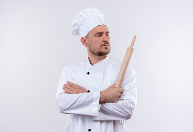 Pewny siebie młody przystojny kucharz w mundurze szefa kuchni stojący z zamkniętą postawą i trzymający wałek do ciasta i patrzący na bok odizolowany na białej ścianie