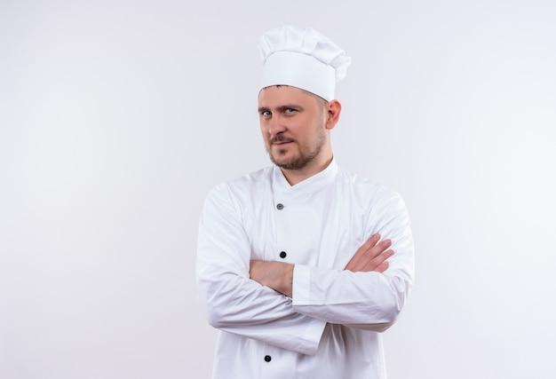 Pewny siebie młody przystojny kucharz w mundurze szefa kuchni stojący z zamkniętą postawą odizolowaną na białej ścianie