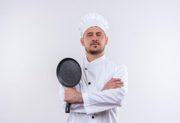 Pewny siebie młody przystojny kucharz w mundurze szefa kuchni stojący z zamkniętą postawą trzymającą patelnię odizolowaną na białej ścianie