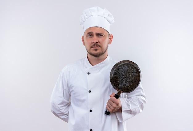 Pewny siebie młody przystojny kucharz w mundurze szefa kuchni trzymając patelnię na izolowanej białej ścianie