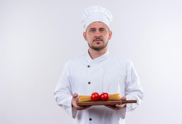 Pewny siebie młody przystojny kucharz w mundurze szefa kuchni trzymający deskę do krojenia z pomidorami i makaronem spaghetti na białym tle na białej ścianie