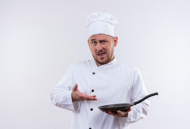 Pewny siebie młody przystojny kucharz w mundurze szefa kuchni trzymający i wskazujący na patelnię odizolowaną na białej ścianie