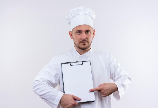 Pewny siebie młody przystojny kucharz w mundurze szefa kuchni trzymający i wskazujący na schowek na białym tle na białej ścianie