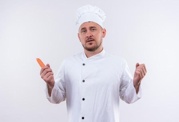 Pewny siebie młody przystojny kucharz w mundurze szefa kuchni trzymający marchewkę odizolowaną na białej ścianie
