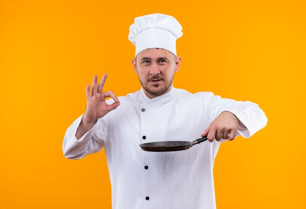Pewny siebie młody przystojny kucharz w mundurze szefa kuchni trzymający patelnię i robiący znak ok odizolowany na pomarańczowej ścianie