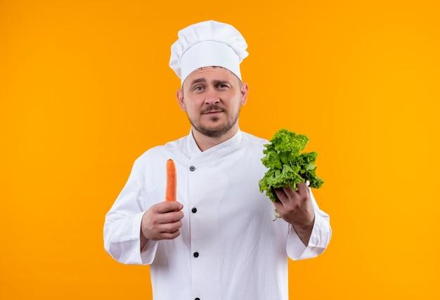 Pewny siebie młody przystojny kucharz w mundurze szefa kuchni trzymający sałatę i marchewkę odizolowanych na pomarańczowej ścianie