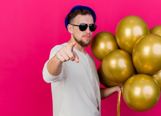 Pewny siebie młody przystojny słowiański facet w kapeluszu imprezowym i okularach przeciwsłonecznych, trzymając balony patrząc i wskazując na przód na białym tle na różowej ścianie z miejscem na kopię