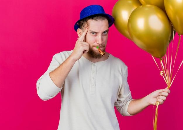 Pewny siebie młody przystojny słowiański imprezowicz w kapeluszu imprezowym, trzymając balony i dmuchawę imprezową, patrząc na przód, robi gest myślenia na białym tle na różowej ścianie