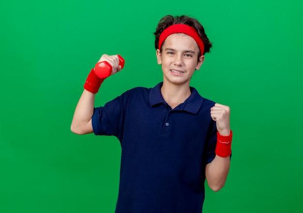 Pewny siebie młody przystojny sportowy chłopak noszący opaskę i opaski na nadgarstki z aparatem ortodontycznym patrząc na przód podnoszący hantle, wykonujący gest tak na białym tle na zielonej ścianie z miejscem na kopię
