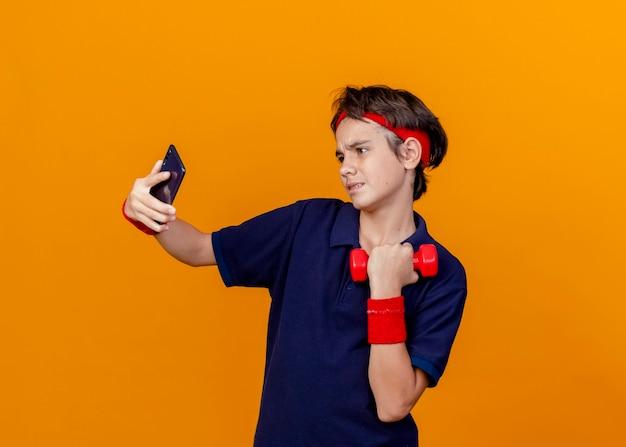 Pewny siebie młody przystojny sportowy chłopak ubrany w opaskę i opaski na rękę z aparatami ortodontycznymi trzymając hantle przy selfie na pomarańczowej ścianie
