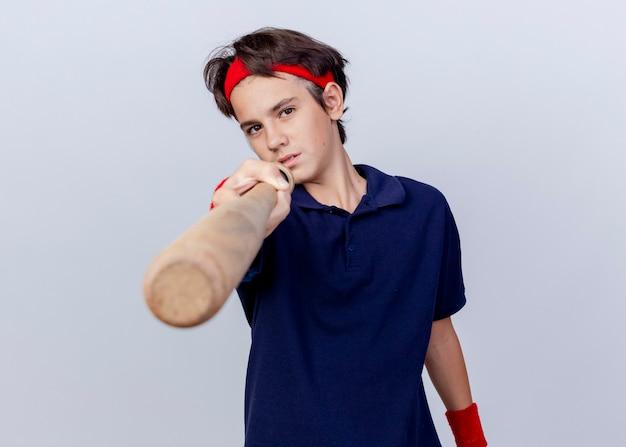 Pewny siebie młody przystojny sportowy chłopiec noszący opaskę i opaski na nadgarstki z aparatami ortodontycznymi patrząc z przodu i wskazując kijem baseballowym z przodu na białym tle na białej ścianie