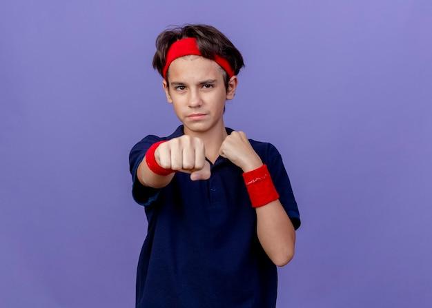 Pewny siebie młody przystojny sportowy chłopiec noszący opaskę i opaski na nadgarstki z aparatami ortodontycznymi patrząc z przodu wyciągając pięść do przodu odizolowany na fioletowej ścianie