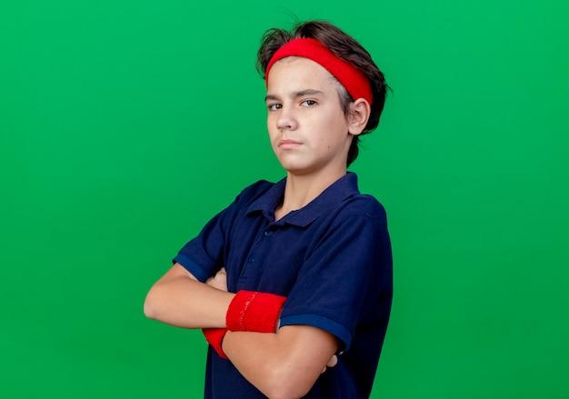 Pewny siebie młody przystojny sportowy chłopiec noszący opaskę i opaski na rękę z aparatami ortodontycznymi stojący z zamkniętą postawą w widoku profilu patrząc na kamerę odizolowaną na zielonym tle z przestrzenią do kopiowania