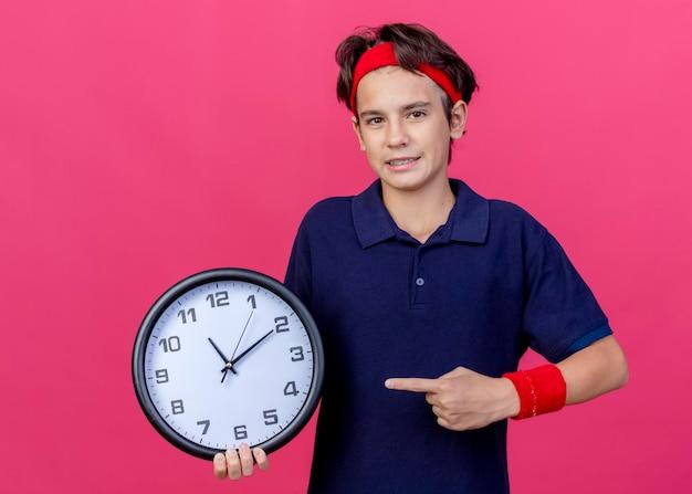 Pewny siebie młody przystojny sportowy chłopiec noszący opaskę i opaski na rękę z aparatami ortodontycznymi trzymający i wskazujący na zegar patrząc z przodu odizolowany na różowej ścianie