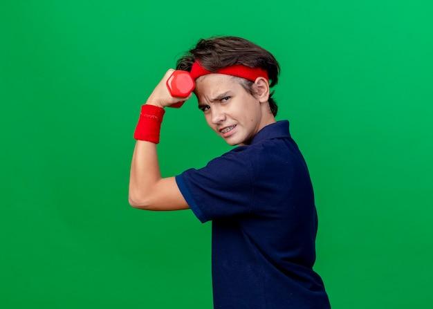Pewny siebie młody przystojny sportowy chłopiec noszący opaskę i opaski na rękę z aparatem ortodontycznym stojący w widoku profilu podnoszący hantle patrząc z przodu odizolowany na zielonej ścianie