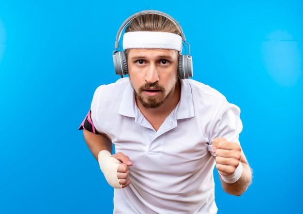 Pewny siebie młody przystojny sportowy mężczyzna nosi opaskę i opaski na rękę i słuchawki